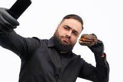 Hombre serio que toma el selfie con la hamburguesa fotografía de archivo libre de regalías
