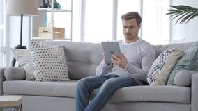 Hombre serio que usa la tableta mientras que se sienta en el sofá almacen de video