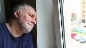 Hombre serio triste con el pelo gris que piensa y que mira hacia fuera la ventana con soledad