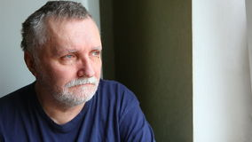 Hombre serio triste que mira hacia fuera la ventana Concepto de la soledad