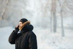 Hombre siberiano que habla en el teléfono al aire libre por día frío en una chaqueta caliente del invierno abajo con la capilla d Fotos de archivo