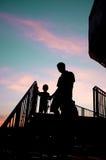 Hombre silueteado y niño que caminan abajo de las escaleras en puesta del sol Imagen de archivo