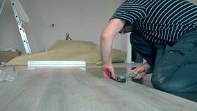 Hombre simple que pone a tableros laminados en piso con el martillo almacen de video