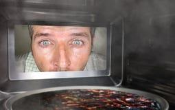 Hombre simulado sucio y divertido en la cocina que mira a través de la microonda o de la pizza del horno que quema quemada hacien fotografía de archivo