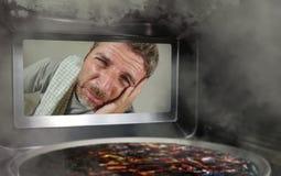 Hombre simulado sucio y divertido en la cocina que mira a través de la microonda o de la pizza del horno que quema quemada hacien foto de archivo