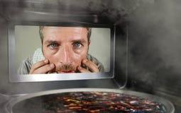 Hombre simulado sucio y divertido en la cocina que mira a través de la microonda o de la pizza del horno que quema quemada hacien fotos de archivo libres de regalías