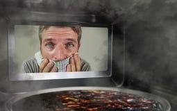 Hombre simulado sucio y divertido en la cocina que mira a través de la microonda o de la pizza del horno que quema quemada hacien imágenes de archivo libres de regalías