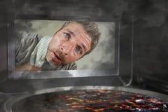 Hombre simulado sucio y divertido en la cocina que mira a través de la microonda o de la pizza del horno que quema quemada hacien foto de archivo libre de regalías