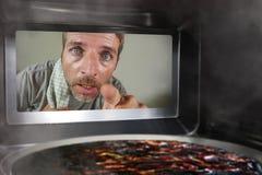 Hombre simulado sucio y divertido en la cocina que mira a través de la microonda o de la pizza del horno que quema quemada hacien imagen de archivo libre de regalías