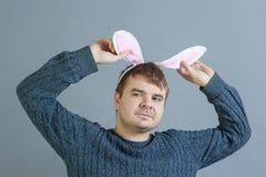 Hombre sin afeitar con los oídos del conejito Un hombre extraño se aferra a sus oídos fotografía de archivo libre de regalías