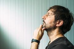 Hombre sin afeitar pensativo con la mano en la barbilla que toma la decisión fotos de archivo libres de regalías