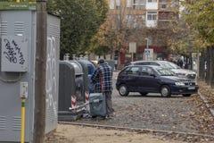 Hombre sin hogar con un bolso de la carretilla que hace compras scavening en la basura fotografía de archivo