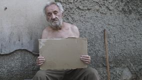 Hombre sin hogar con una muestra que pide ayuda almacen de video