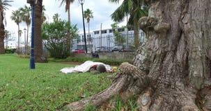Hombre sin hogar cubierto que duerme en el parque metrajes