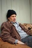 Hombre sin hogar durmiente con la botella de vino en un saco Imágenes de archivo libres de regalías