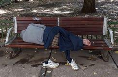 Hombre sin hogar durmiente en el banco Fotos de archivo