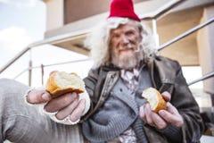 Hombre sin hogar envejecido que comparte su pan imagen de archivo