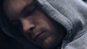 Hombre sin hogar joven que duerme en la calle de la ciudad en la noche, concepto social de los problemas almacen de video