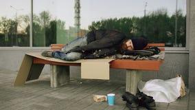 Hombre sin hogar joven que intenta dormir debajo de la chaqueta en banco en la acera imagen de archivo libre de regalías