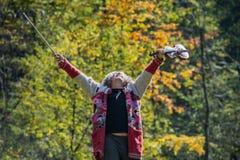 Hombre sin hogar mayor con el suéter viejo rasgado que celebra vida fotos de archivo