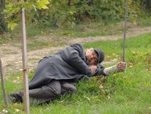 Hombre sin hogar pobre que duerme en la hierba Imagenes de archivo