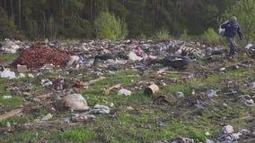 Hombre sin hogar que busca artículos y la comida útiles para la supervivencia entre los desperdicios en montones de basura de la  almacen de metraje de vídeo