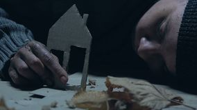 Hombre sin hogar que detiene la casa del papel, el hogar perdido perdido y a la familia, crisis de vivienda almacen de metraje de vídeo