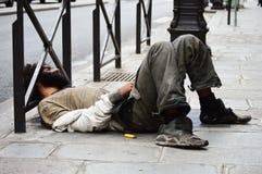 Hombre sin hogar que duerme en la calle en París Foto de archivo libre de regalías