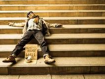 Hombre sin hogar que duerme en las escaleras foto de archivo