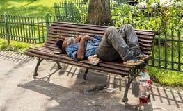 Hombre sin hogar que duerme en un banco en luz del día Imagen de archivo libre de regalías