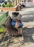 Hombre sin hogar que duerme en un banco en luz del día Foto de archivo libre de regalías