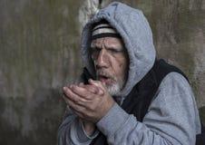 Hombre sin hogar que frota sus manos junto que intentan mantener caliente Fotos de archivo