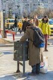 Hombre sin hogar que limpia un compartimiento de basura Foto de archivo libre de regalías