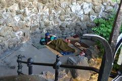 Hombre sin hogar que miente en la tierra y que lee un libro Imagen de archivo libre de regalías