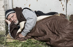 Hombre sin hogar que pone en un saco de dormir viejo en la cartulina Imágenes de archivo libres de regalías