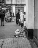 Hombre sin hogar que se sienta en la lectura del pavimento Imágenes de archivo libres de regalías