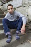 Hombre sin hogar que se sienta en las escaleras Fotos de archivo libres de regalías