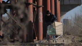 Hombre sin hogar que toma la botella plástica para reciclar almacen de metraje de vídeo