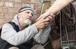 Hombre sin hogar que toma un woman& x27; mano de s Foto de archivo
