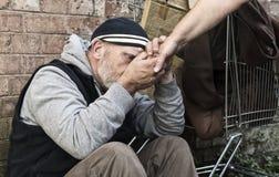 Hombre sin hogar que toma un woman& x27; mano de s Imagenes de archivo