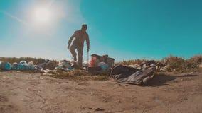 Hombre sin hogar sucio en el vídeo de la cámara lenta de la descarga persona destechada sin hogar que busca la comida en forma de almacen de metraje de vídeo