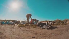 Hombre sin hogar sucio en el vídeo de la cámara lenta de la descarga persona destechada sin hogar que busca la comida en una desc almacen de metraje de vídeo