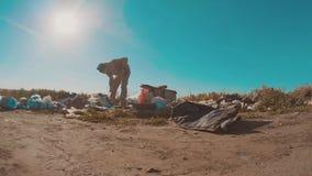Hombre sin hogar sucio en el vídeo de la cámara lenta de la descarga persona destechada sin hogar que busca la comida en una form almacen de video