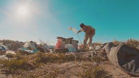 Hombre sin hogar sucio en la forma de vida del vídeo de la cámara lenta de la descarga persona destechada sin hogar que busca la  almacen de video