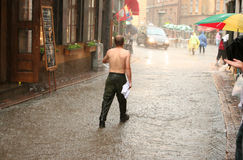 Hombre sin la camisa que recorre en la lluvia Imagen de archivo libre de regalías