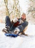 Hombre Sledging a través del arbolado Nevado imagen de archivo libre de regalías