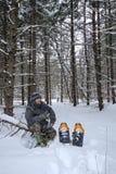 Hombre Snowshoeing en bosque Fotografía de archivo