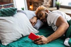 Hombre soñoliento agradable que miente en la cama con su teléfono imagen de archivo libre de regalías