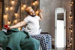 Hombre soñoliento agradable que sostiene su smartphone en las manos imagenes de archivo