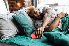 Hombre soñoliento agradable que toma su teléfono móvil fotos de archivo libres de regalías